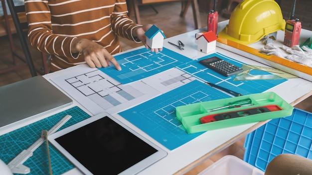 Frauenarchitekt, der blaupausen zeichnet, um alte küche diy umgestalten, die am schreibtisch arbeitet.