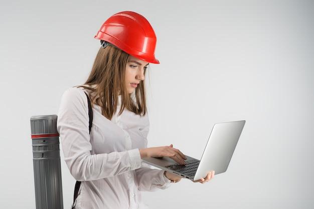 Frauenarchitekt steht mit einem rohr und einem holdinglaptop