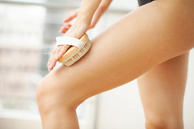Frauenarm hält trockene bürste oben auf ihrem bein, cellulite-behandlung und trockenes bürsten.