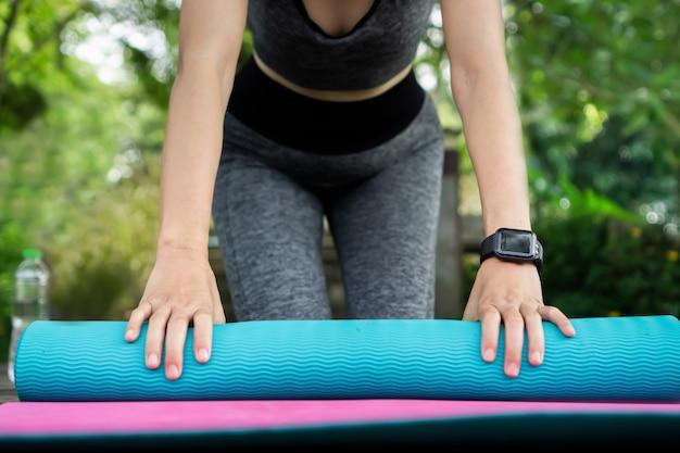 Frauenarm trägt intelligente uhr, die yogamatte faltet