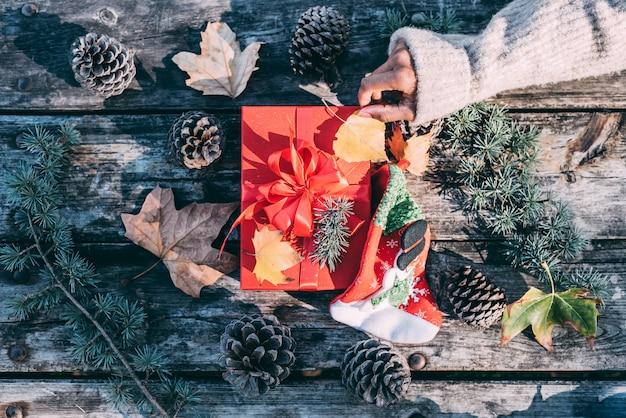Frauenarme, die draußen weihnachtsdekoration in einer hölzernen tabelle tun