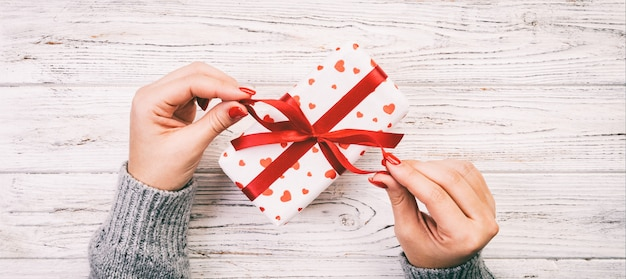 Frauenarme, die geschenkbox halten