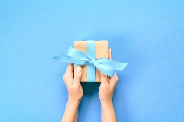 Frauenarme, die geschenkbox mit blauem band auf blau halten