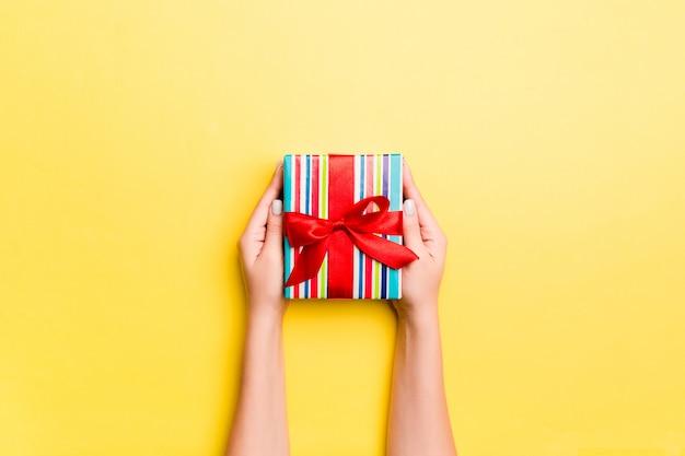 Frauenarme, die geschenkbox mit farbigem band auf gelbem tabellenhintergrund halten