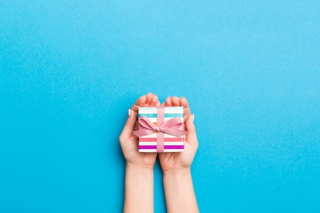 Frauenarme, die geschenkbox mit farbigem band halten
