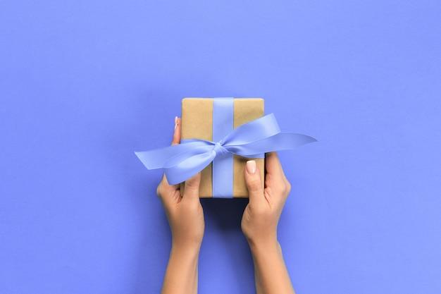 Frauenarme, die geschenkbox mit purpurrotem band auf farbhintergrund, draufsicht halten