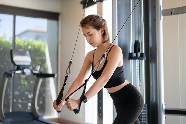 Frauenarme machen kabelfliegenübung im fitnessstudio.