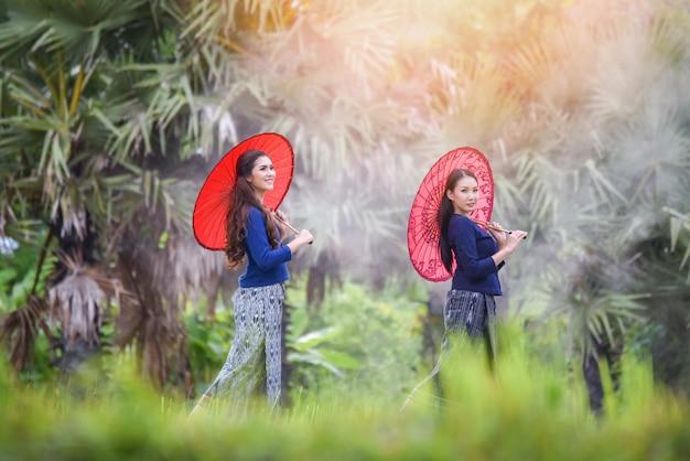 Frauenasien-landwirt im glücklächeln des reisfeldes schönen halten regenschirm