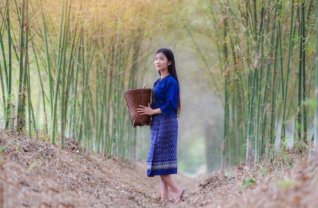 Frauenasien-landwirt im lächeln der jungen frau der bambuswaldnatur lebenskleidestamm