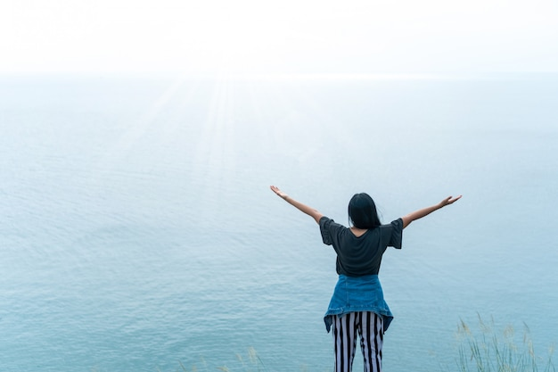 Frauenaufstiegshände bis zum himmelfreiheitskonzept mit blauem himmel.