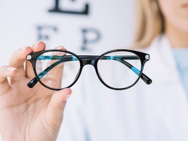 Frauenaugenarzt, der der kamera ein paar brillen zeigt
