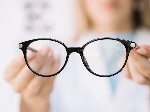 Frauenaugenarztdoktor, der paar lesebrille zeigt