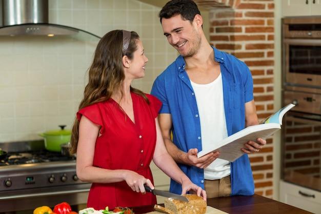 Frauenausschnitt-brotlaib während mann, der zu hause das rezeptbuch in der küche überprüft