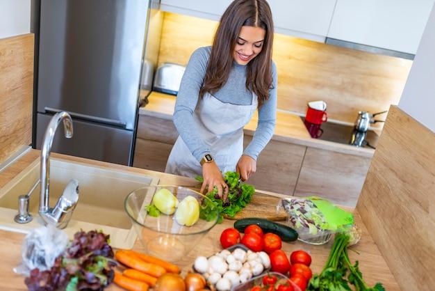 Frauenausschnittkopfsalat, der abendessen in der küche zubereitet
