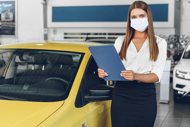 Frauenautoverkäufer, der nahe neuwagen steht, der schützende gesichtsmaske im autohaus trägt