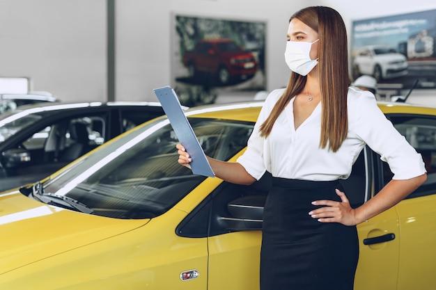 Frauenautoverkäufer, der nahe neuwagen steht, der schützende gesichtsmaske trägt
