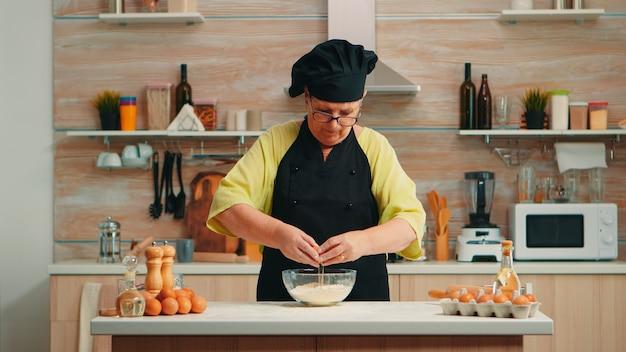 Frauenbäckerin, die eier in mehl nach traditionellem rezept in der heimischen küche knackt. pensionierter älterer koch mit bone, von hand mischen, in glasschüssel gebäckzutaten kneten und hausgemachten kuchen backen
