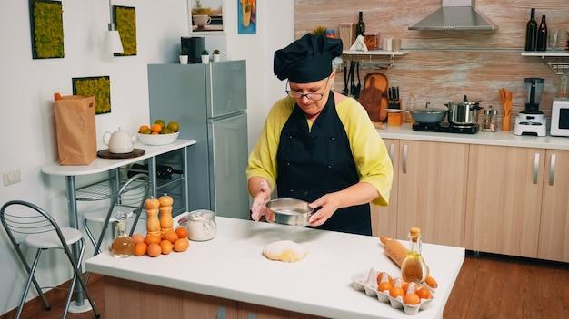 Frauenbäckerin, die mehl auf brotteig mit metallischem sieb auf dem tisch in der küche siebt. glücklicher älterer koch mit gleichmäßiger mischbesprengung, die beim backen von traditionellem brot durch sieben rohe zutaten verteilt