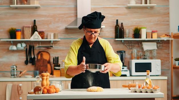 Frauenbäckerin, die mehlmetallsieb verwendet, das hausgemachte kuchen zubereitet. glücklicher älterer koch mit bone, der rohzutaten zum backen von traditionellem brotbestreuen zubereitet, in der küche siebt.