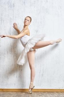Frauenballerina, die in tutu- und spitzenschuhen tanzt