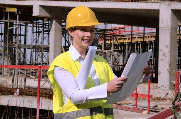 Frauenbauingenieur in der baustelle, die architekturpläne steuert