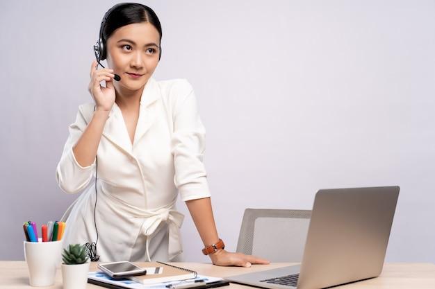 Frauenbediener im headset, das im büro über lokalisiertem weißem hintergrund steht
