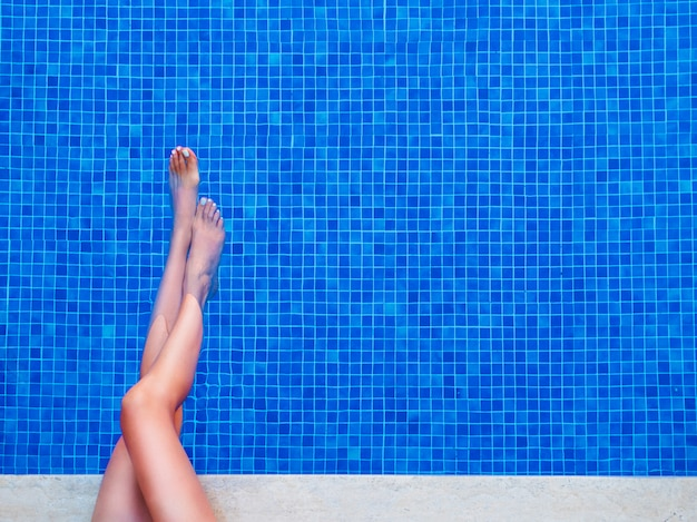 Frauenbeine beim genießen am schwimmbad.