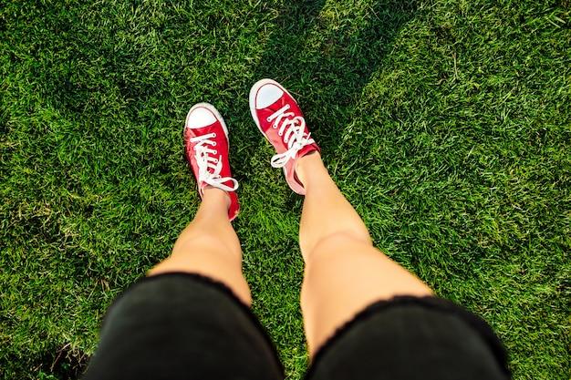 Frauenbeine, die auf gras im park stehen
