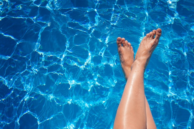 Frauenbeine, die im tropischen swimmingpool spritzen