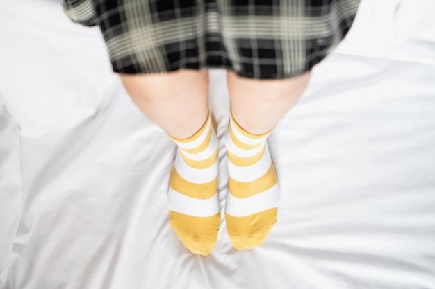 Frauenbeine in abwechselnden sockenfarben, seitenständer auf weißem stoffboden.