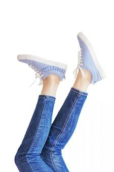 Frauenbeine in blue jeans auf dem weißen hintergrund lokalisiert