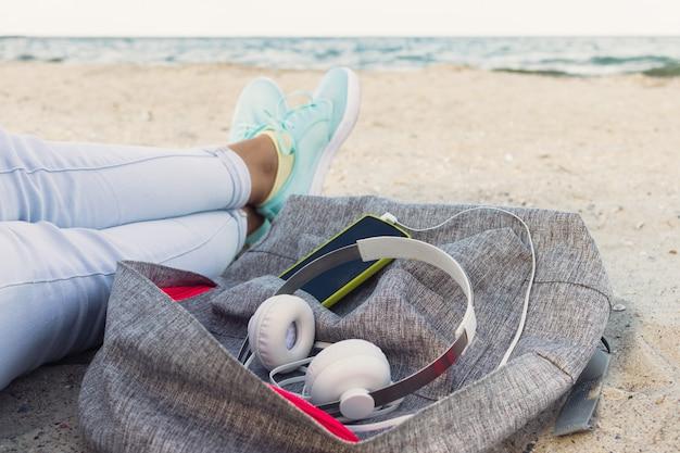 Frauenbeine in jeans und turnschuhen, rucksack, kopfhörer und smartphone am strand im sommer