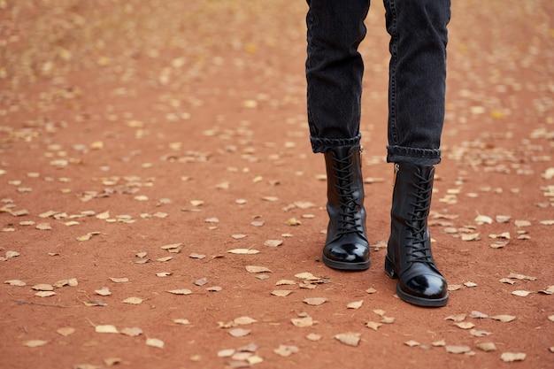 Frauenbeine in modischen schwarzen herbstlederstiefeln und trendigen schwarzen jeans.