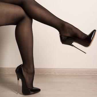 Frauenbeine in schwarzem fetisch glänzendem lackleder stiletto hoch er