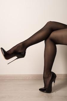 Frauenbeine in schwarzen fetisch glänzenden lackleder-stöckelschuhen mit knöchelriemen