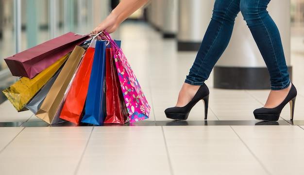 Frauenbeine mit einkaufstüten vor dem hintergrund eines einkaufszentrums