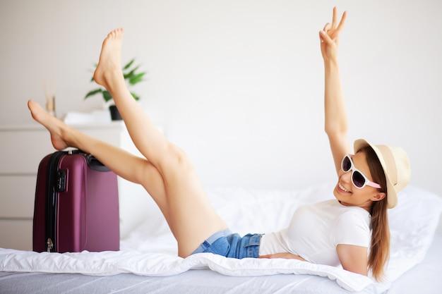 Frauenbeine oben angehoben auf das gepäck, junge frau zu hause, die in bett legt. das weiße schlafzimmer.