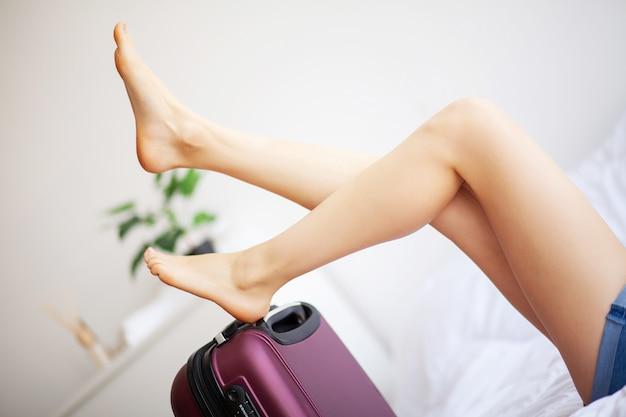 Frauenbeine oben angehoben auf das gepäck, junge frau zu hause, die in bett legt. das weiße schlafzimmer