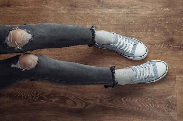 Frauenbeine tragen in zerrissenen jeans und turnschuhen, die auf einem holzboden sitzen.
