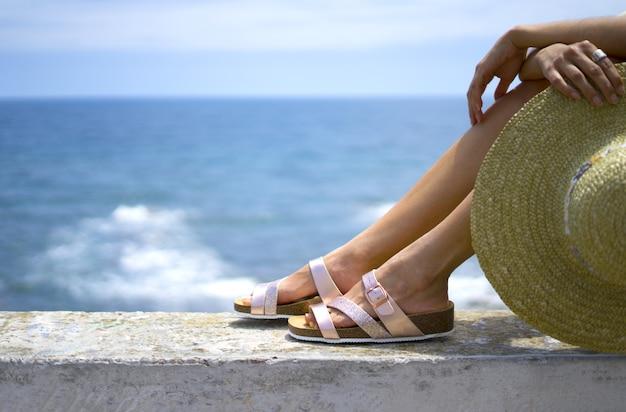 Frauenbeine tragen rosa sandalen an den füßen und halten einen strohhut am meer