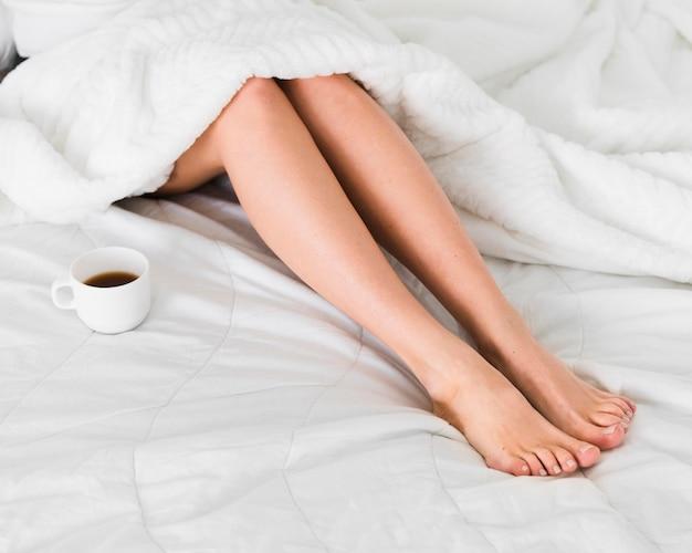 Frauenbeine und tasse kaffee