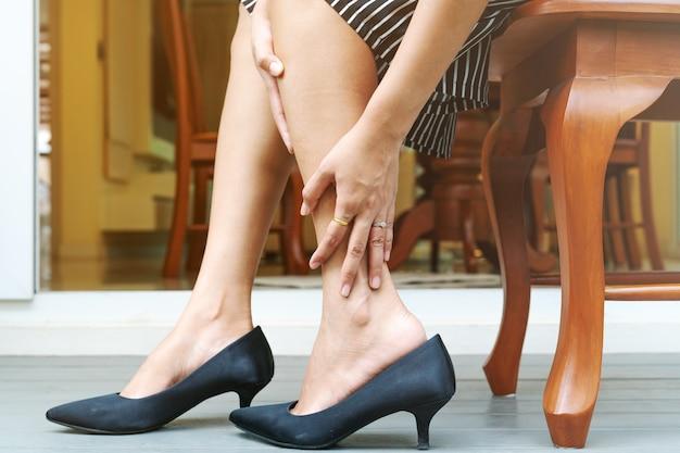 Frauenbeinkrampf von tragenden schuhen der hohen absätze, gesundheitswesenkonzept