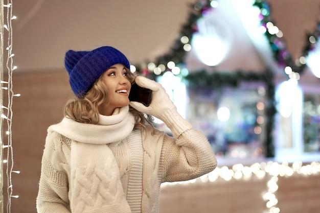 Frauenbenennen beglückwünschen mit weihnachten oder neuem jahr. frau mit smartphone an der festlichen messe