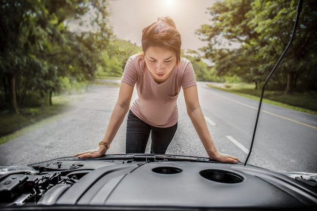 Frauenbeobachtung sie öffnete die motorhaube kaputtes auto an der seite sehen sie motoren, die beschädigt sind oder nicht