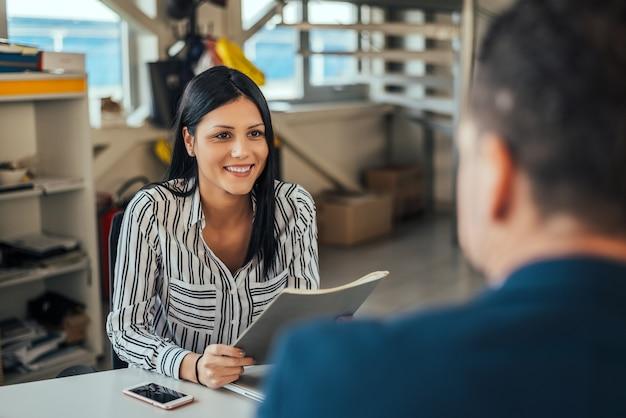 Frauenberater, der mit kunden im büro spricht.