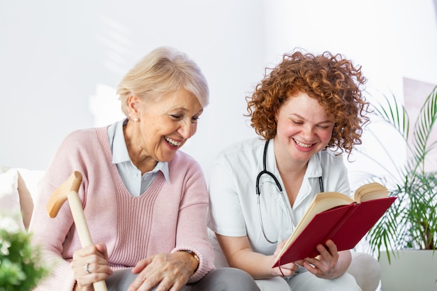 Frauenbetreuerin, die ein buch liest, während sie mit glücklicher älterer frau am pflegeheim sitzt.