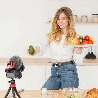 Frauenblogger, der teller der früchte hält