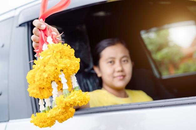 Frauenblumengirlande in der hand und beten im neuwagen für glückliches