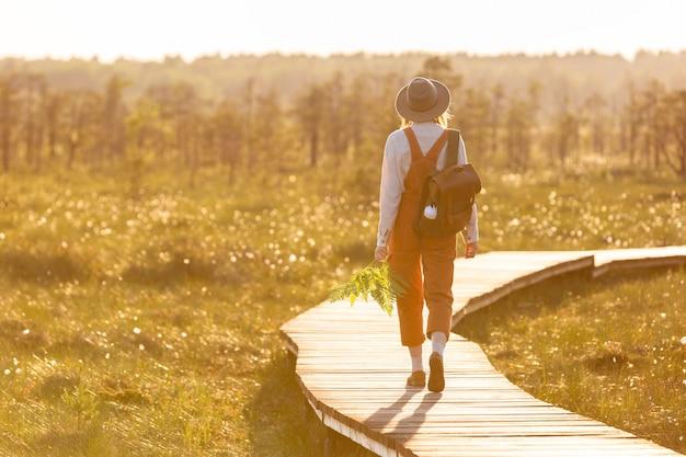 Frauenbotanikerin mit rucksack auf ökologischem wanderweg im sommer im freien. naturforscher, der wildtier- und ökotourismus-abenteuer auf dem weg erkundet