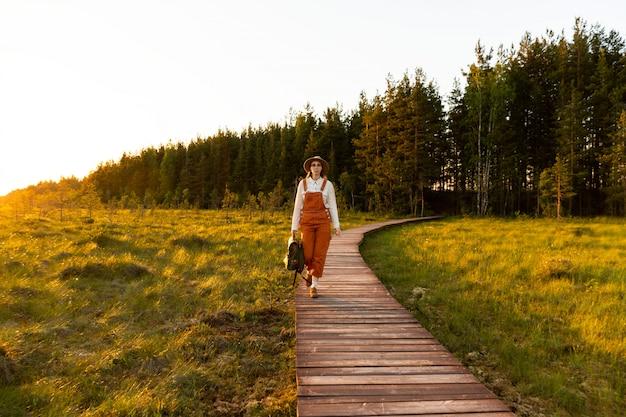 Frauenbotanikerin mit rucksack auf ökologischem wanderweg im sommer im freien. naturforscher, der wildtiere und ökotourismus erforscht